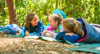 Three girls in sleeping bags laughing and relaxing on the forest floor