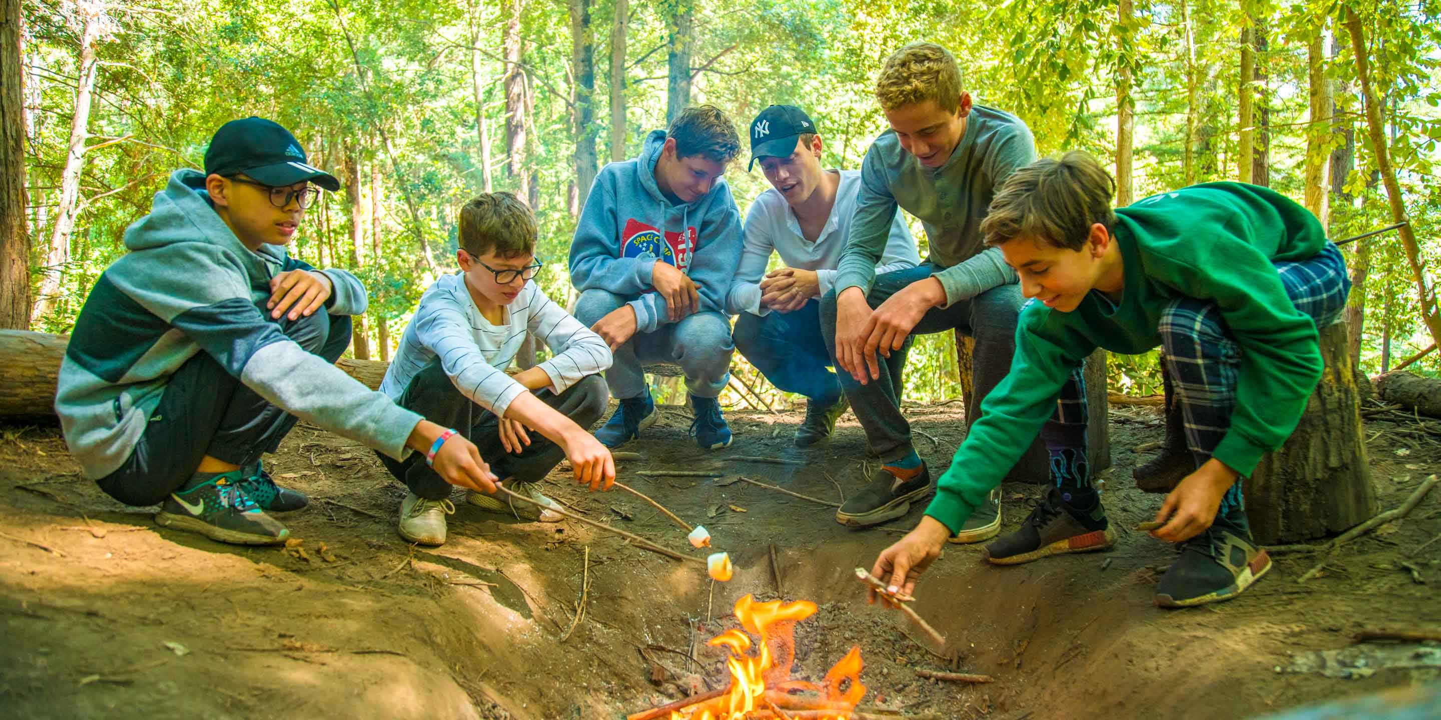 Group of campers roast marshmallows over fire