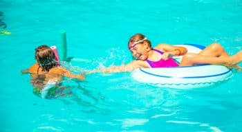 Girls swimming with pool noodles