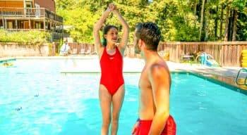 Camper prepares to dive backward into pool