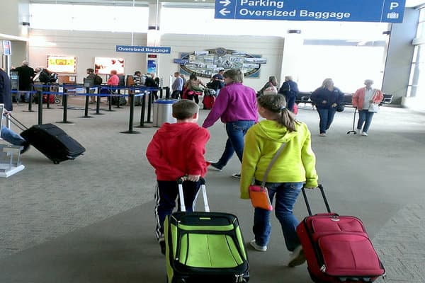 Two kids walking through an airport with luggage