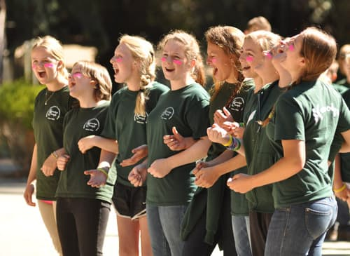 Counselors with linked arms sing a song