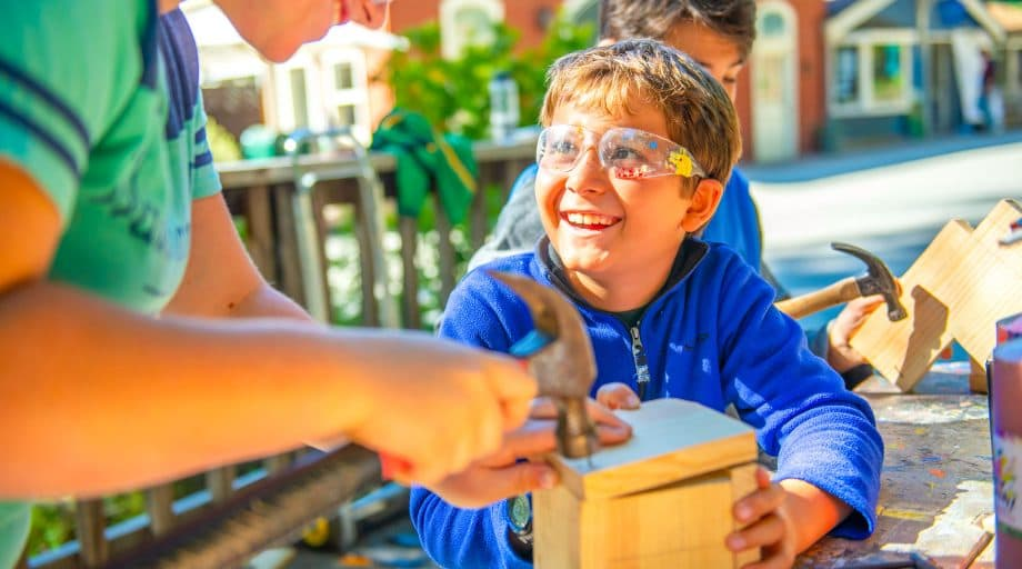 Young boy smiles while doing carpentry