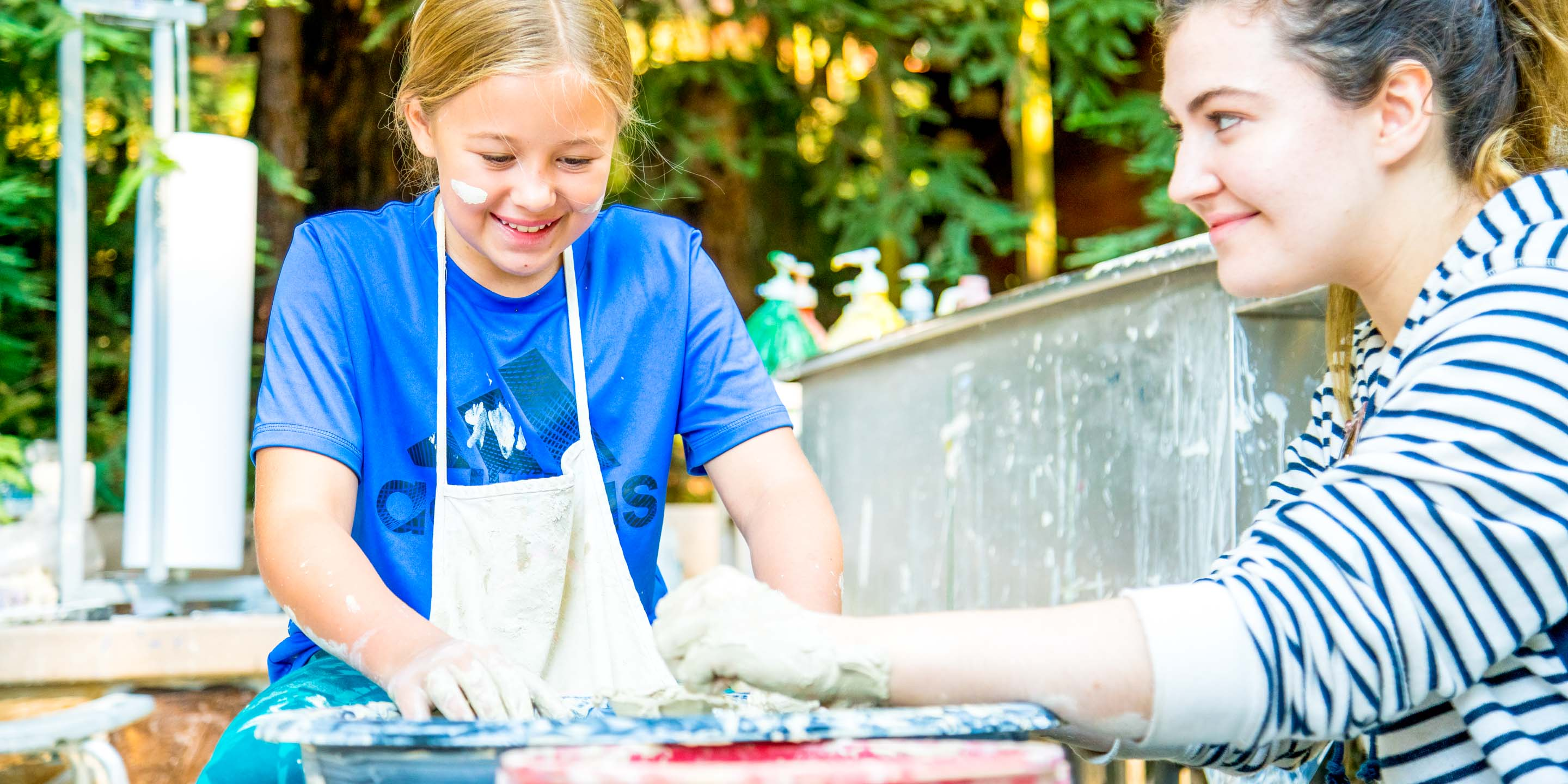 Girl does pottery at summer camp