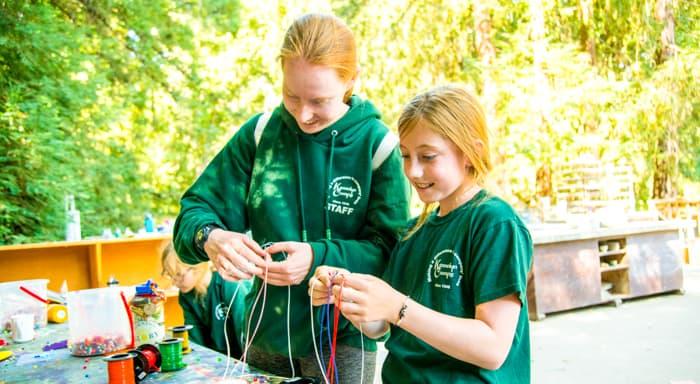 Girls making friendship bracelets outside