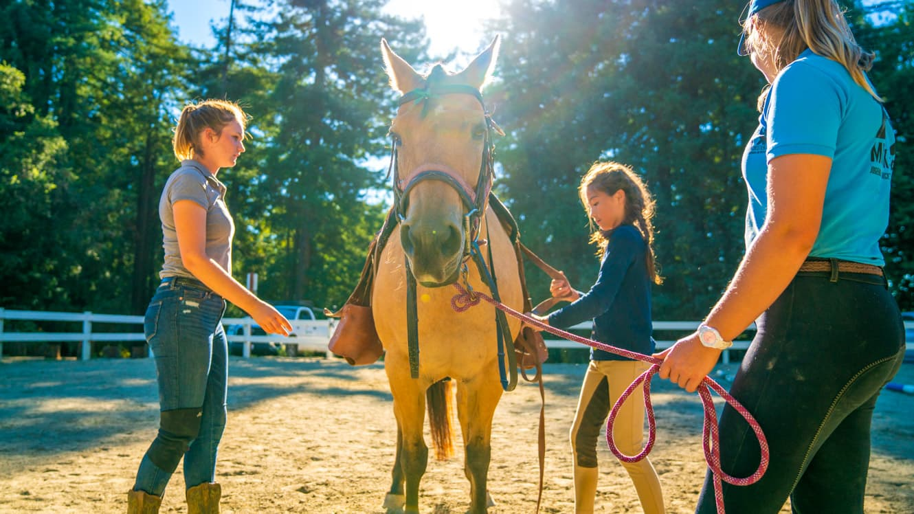 Camper and staff prepare horse for riding
