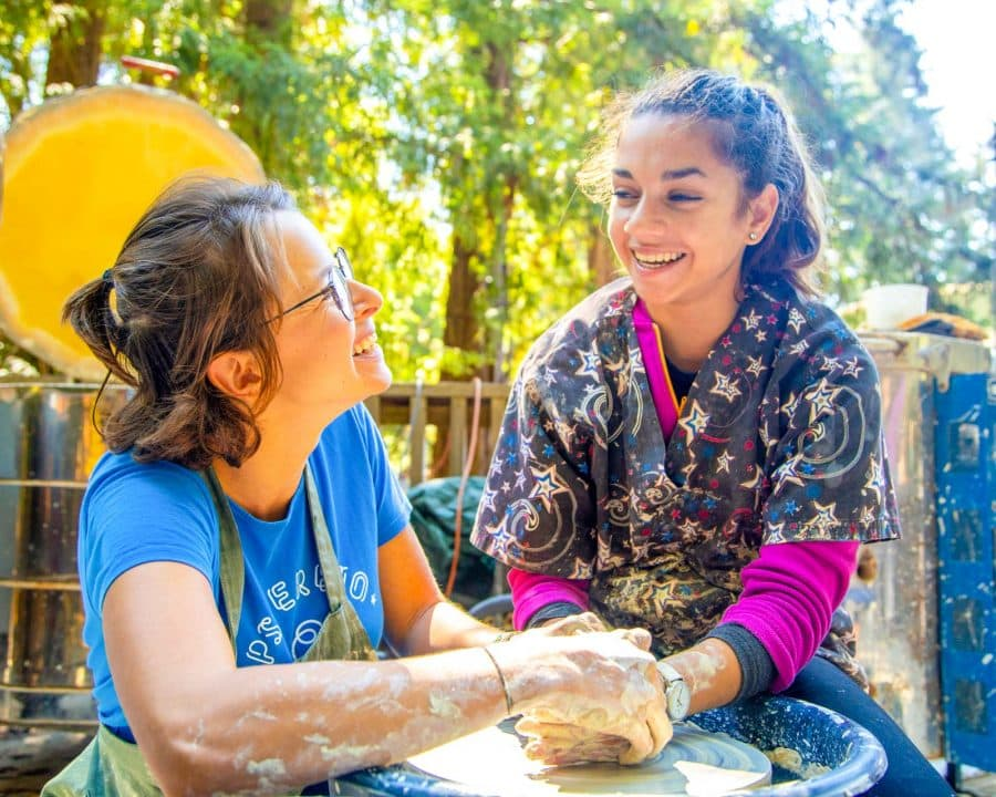 Staff member helps girl make ceramics at summer camp