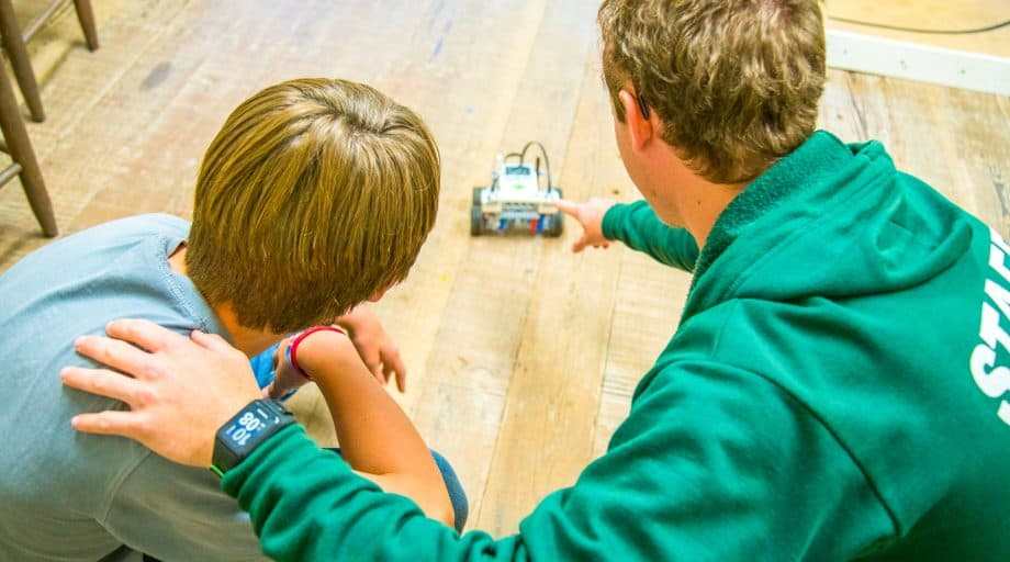 Counselor and camper watch robot drive