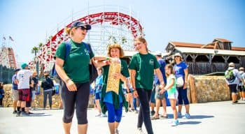 A counselor and two campers walk around the boardwalk with popcorn