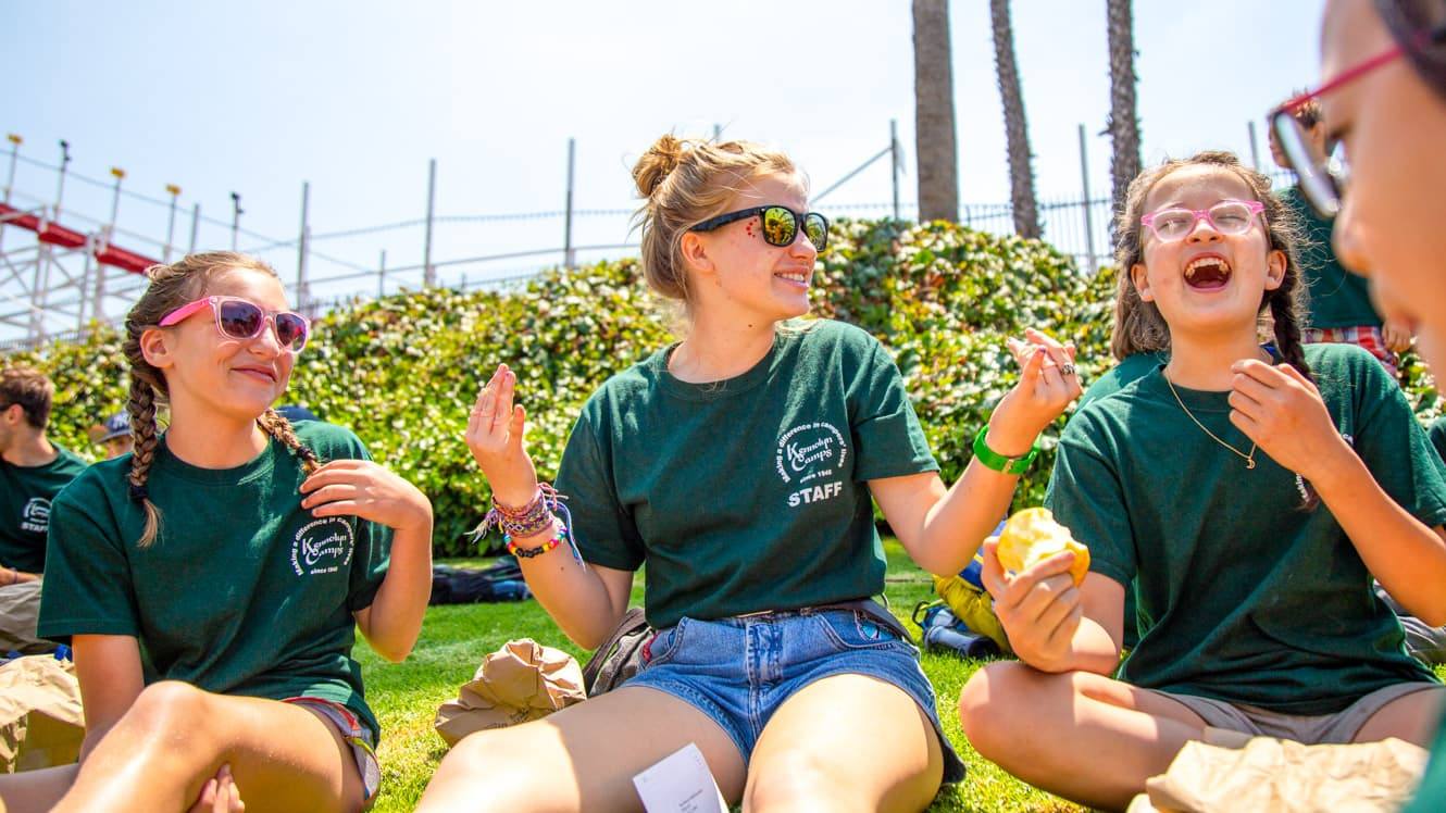 Counselor talks with campers on boardwalk trip