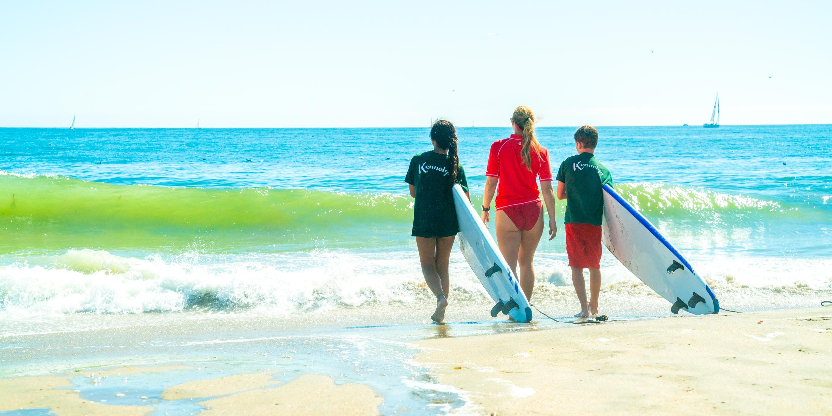 Counselor and campers walk down beach with surfboards