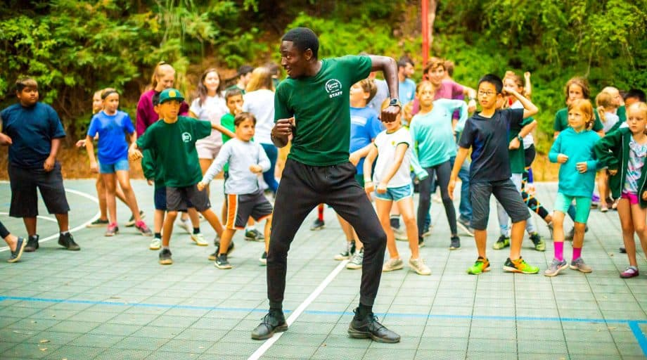 Staff member leads campers in dance