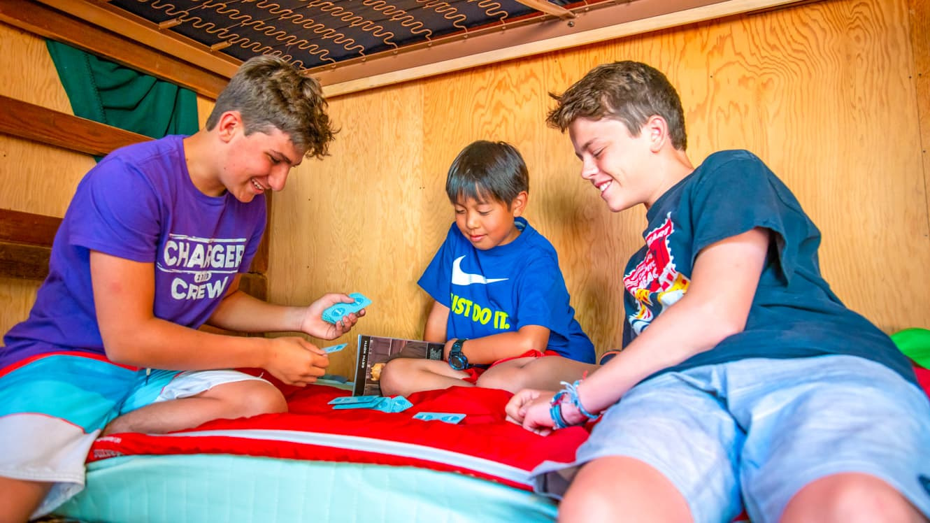 Boys play cards on camp cabin bunk