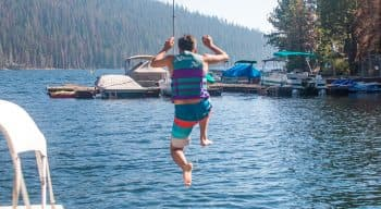 A camper in a life vest jumps off the dock into the lake