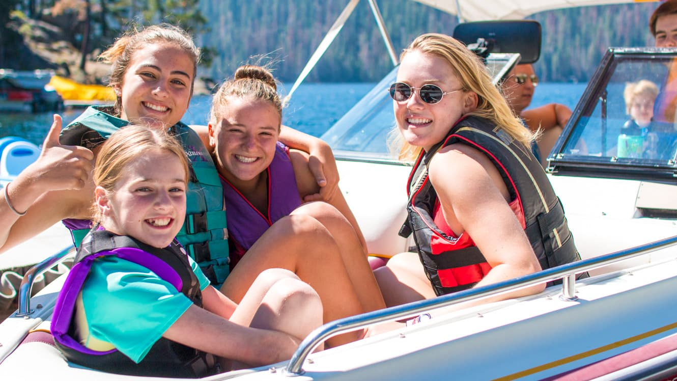 Campers in speed boat smile at camera