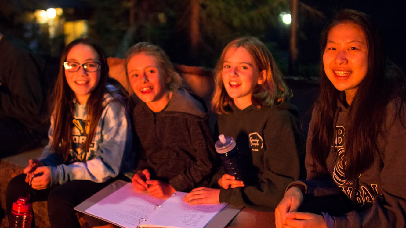 Campers sit in light of campfire
