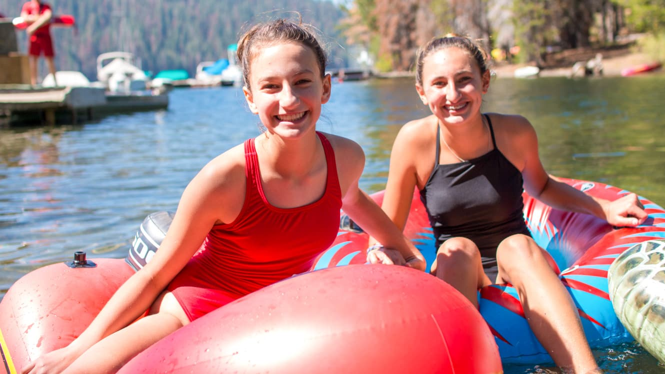 Campers float on inflatables on lake