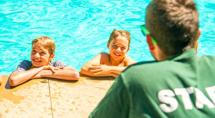 Two campers hanging out poolside with a staff member