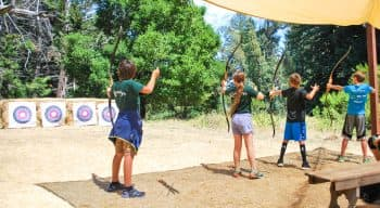 Four campers aiming bow and arrows at targets