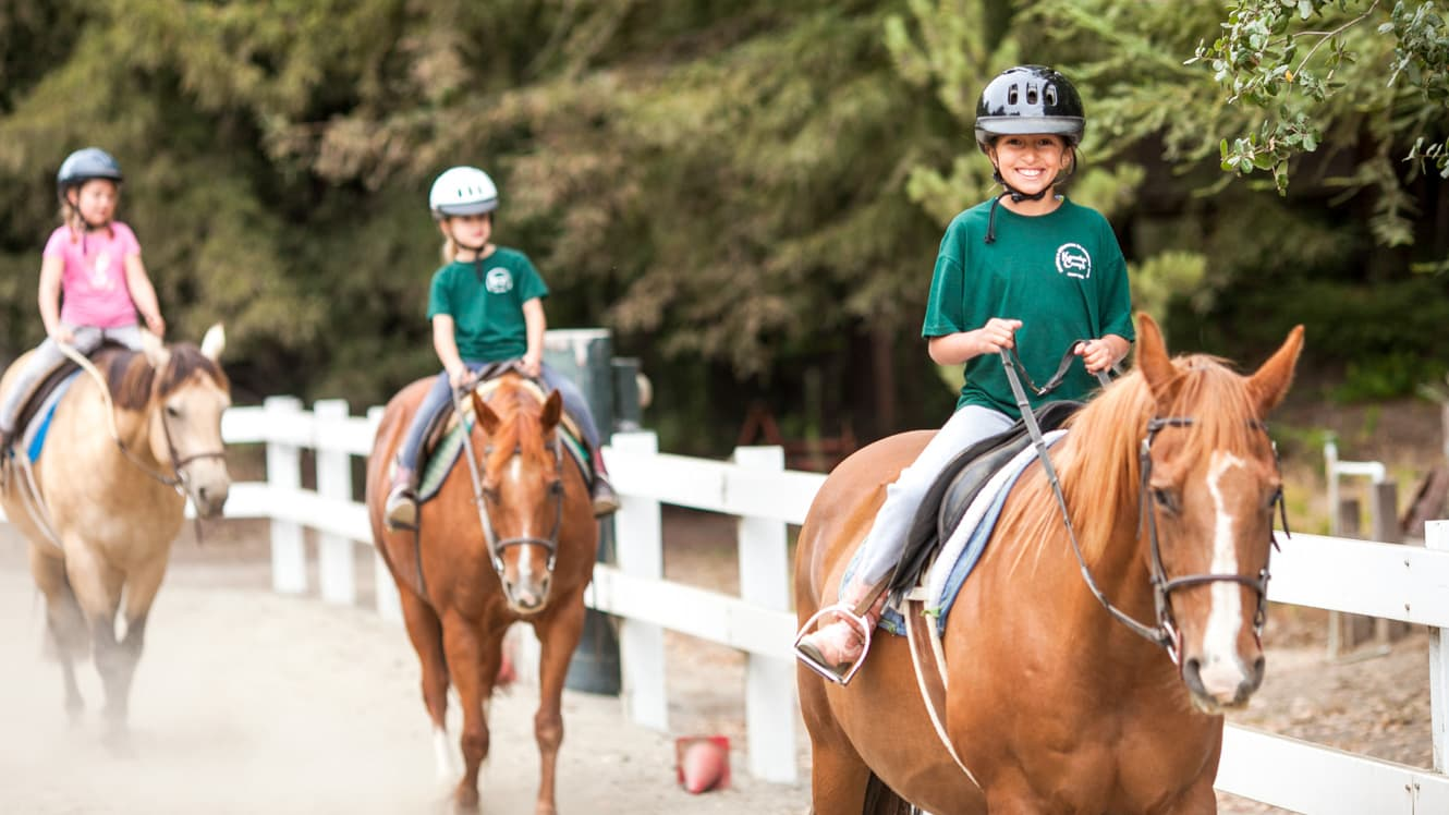 Day campers ride horses in paddock