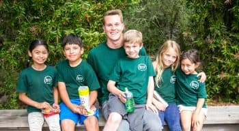 A counselor smiling with a group of campers