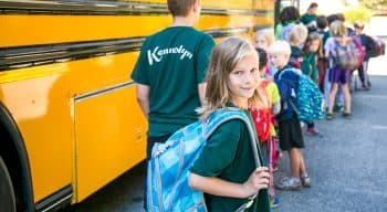 A camper looks at the camera while in line for the bus