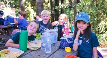 Campers at a picnic table eating lunch and smiling