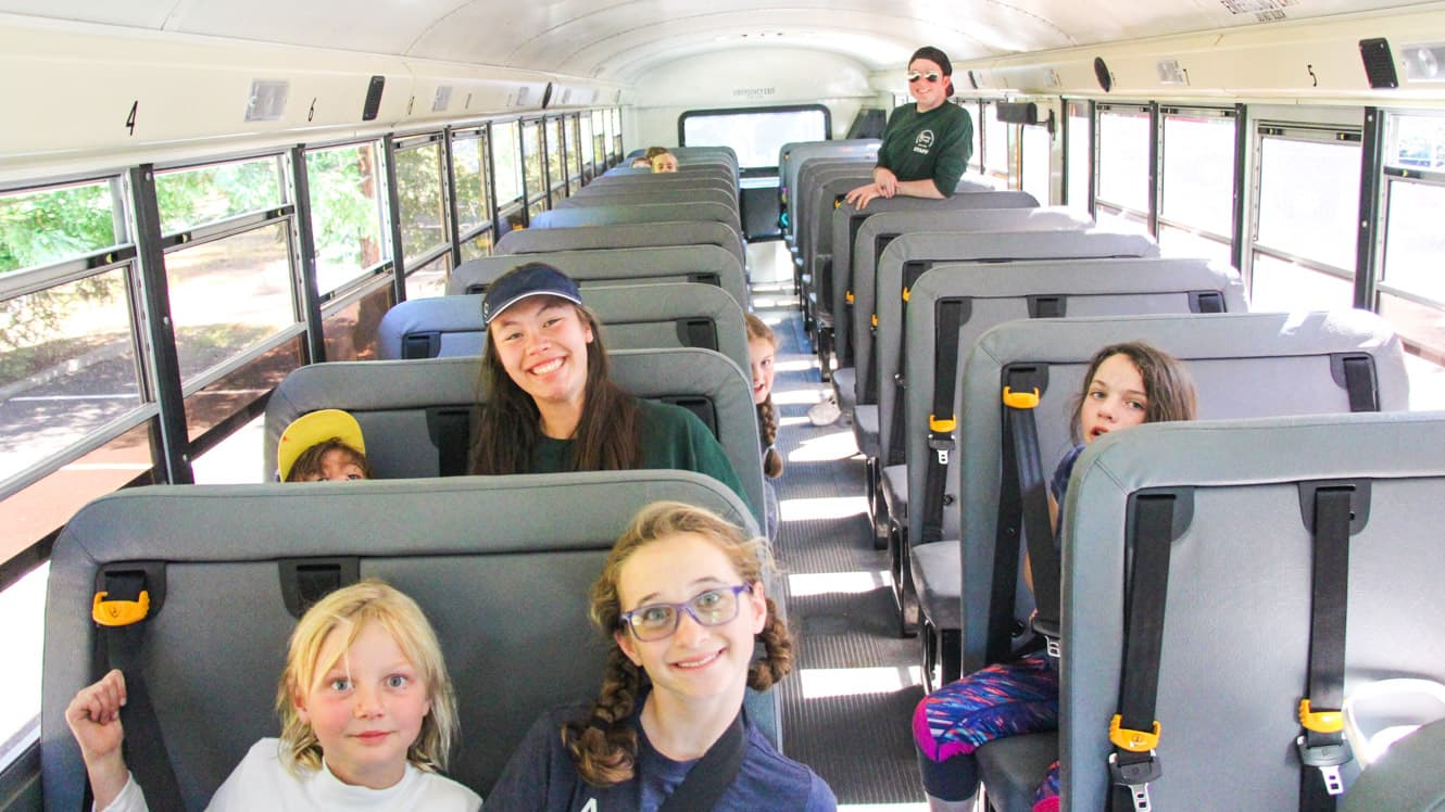 Day campers sit on bus