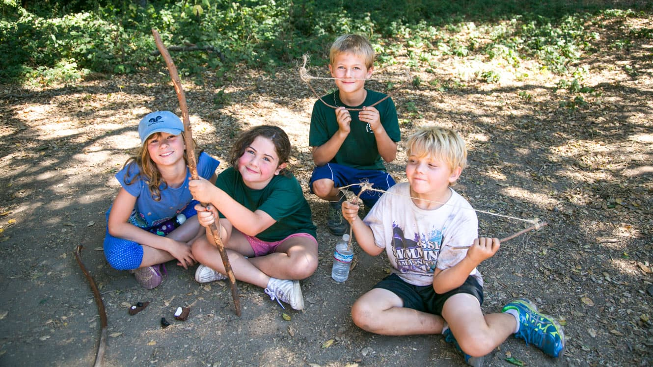 Day campers sit on ground with stick creations