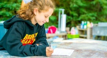A girl writing a letter with a sweatshirt on