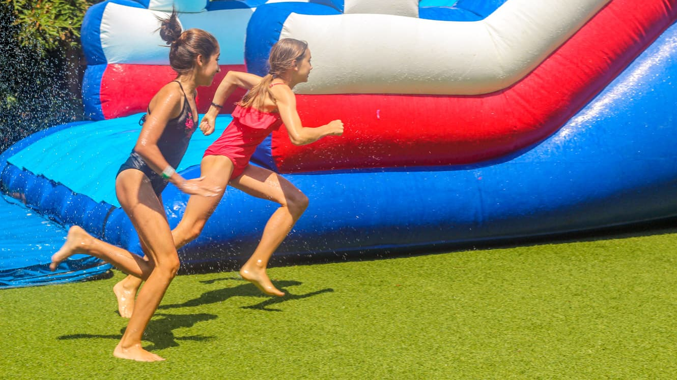 Girls running on grass next to inflatable waterslide