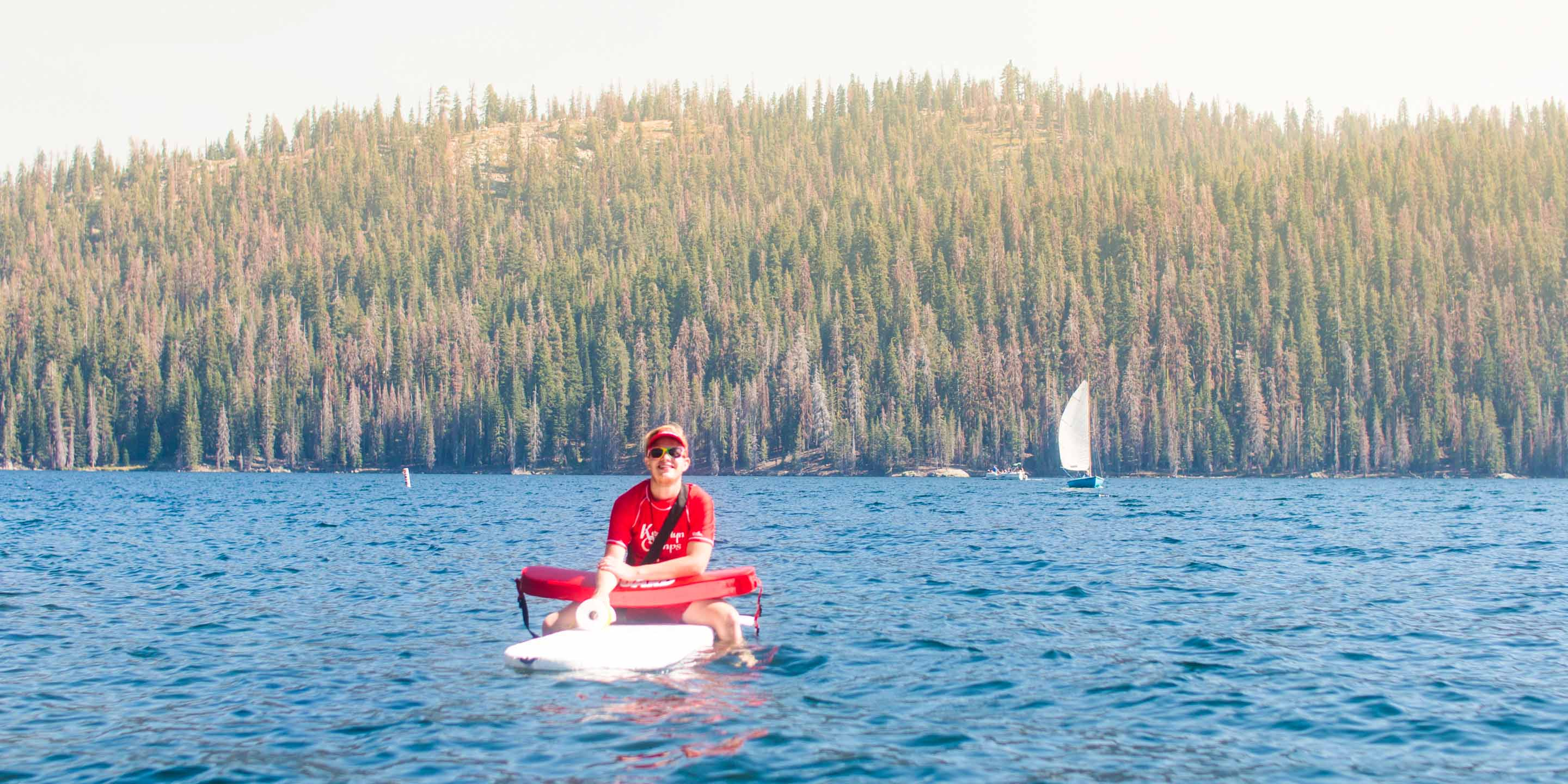 Lifeguard sits on surfboard on Huntington Lake