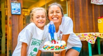 A counselor and a camper pose in back of a birthday cake