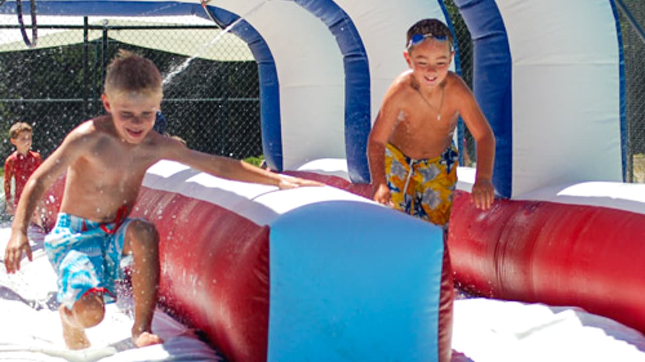 Boys running through inflatable waterslide