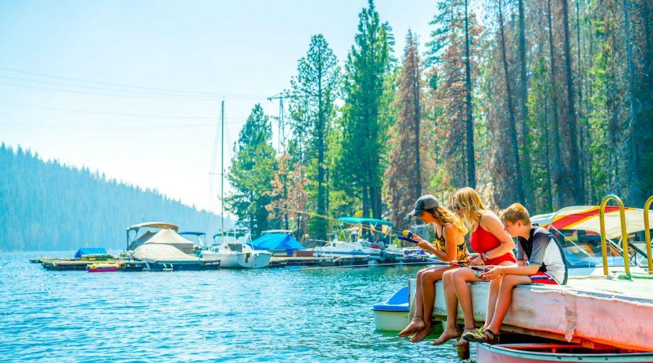 Three kids fishing on a dock