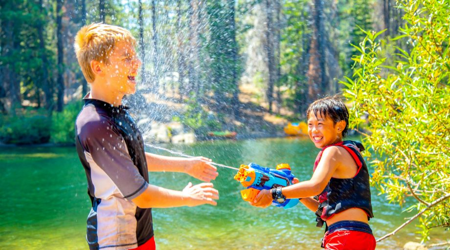 Two boys having a water gun fight