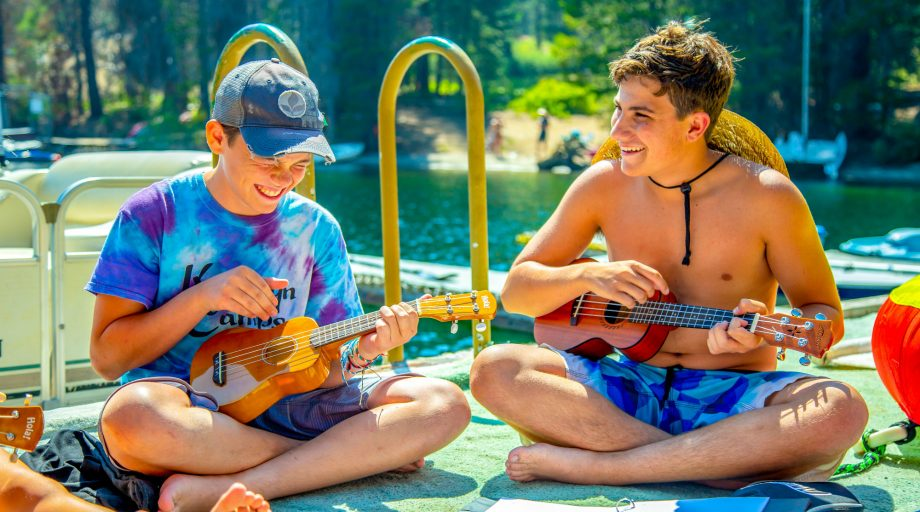 Two boys playing ukeleles on a dock