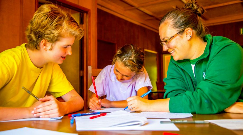 Two counselors helping a girl write