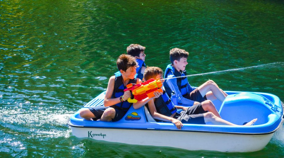 four boys on a paddle boat