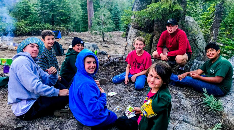 campers around a campfire in the woods
