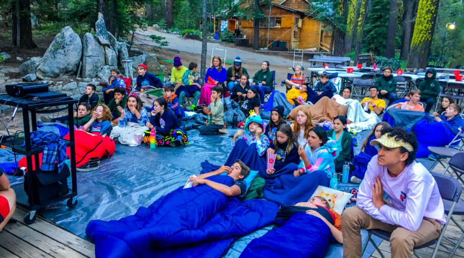 campers in sleeping bags sit outside to watch a movie
