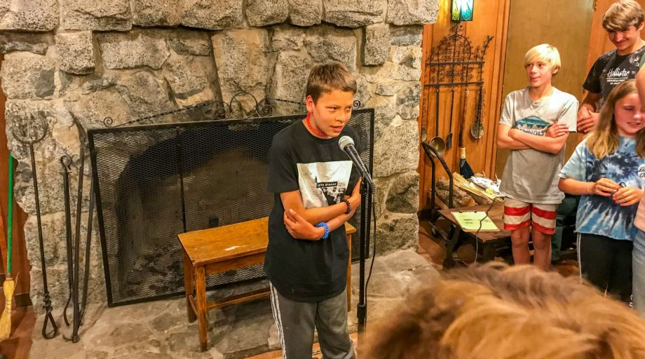 A boy speaking into a microphone in a lobby