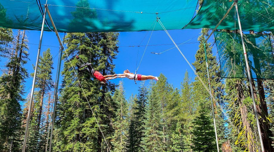 Two kids performing a trapeze stunt