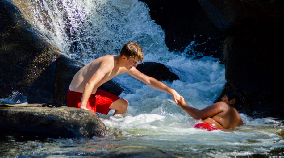 Boys goofing off in a waterfall