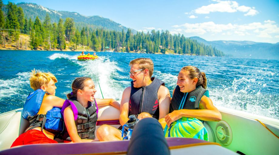 Four kids on a boat with a tube behind them